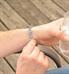 Man showing custom premium laser engraving on silver medical ID tag