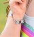 Little girl showing medical alert tag on colorful medical ID bracelet