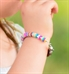 Young girl wearing colorful beaded medical ID bracelet with multicolored disc beads