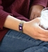 Woman holding a drink wearing adjustable medical ID bracelet with magnetic closure in oil slick, color changing finish and mesh band.