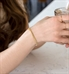Woman holding glass and wearing delicate gold medical alert chain bracelet