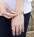 Woman wearing SmartSize Medical ID Bracelet. Copper tone leather band. Holds tag to show engraving on back of rose med ID tag