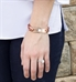 Woman wearing SmartSize Med ID Bracelet. Copper tone leather band with adjustable chain. Rose tone La Petite tag