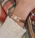 Smartly-dressed woman wearing Avery SmartSize Med ID Bracelet showing copper tone leather bands and rose tone La Petite ID tag