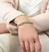 Woman wearing silver crystal and pearl medical alert bracelet with teal accents