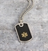 Black medical alert dog tag necklace with ball chain on cement background