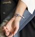 Woman wearing decorative silver medical alert tag on beaded bracelet