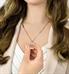 Woman showing custom laser engraved rose gold medical alert pendant necklace