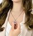 Woman showing custom laser engraving circular medical alert medallion necklace