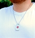 Man wearing silver-tone stainless Medical Alert Dog Tag on a chain. Rounded corners, beveled ridged edge, red caduceus