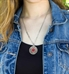 Woman wearing round silver tone stainless pendant with antique patina and clear layer over intricate pattern. Flat oval chain