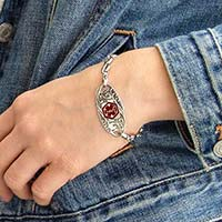 Woman wearing the Oval Filigree Red Caduceus Medical ID Tag, a stainless tag with antique finish, scrolling filigree design