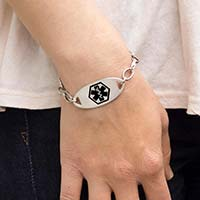 Woman wearing the oval-shaped silver-tone Stainless Black Oval Medical ID Tag with black medical caduceus on an LH bracelet