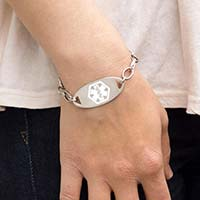 Woman wearing the silver-tone Stainless White Oval Medical ID Tag with white caduceus symbol in the center on an LH bracelet
