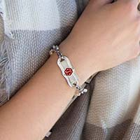 Woman wearing silver tone stainless steel La Petite Medical ID tag with red caduceus on a Lauren's Hope med ID bracelet