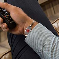 Man holding TV remote wearing a LH bracelet with the Oval Border Medical ID Tag, a stainless tag with rope detail on the edge