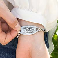 Woman wearing Black Macrame Medical ID Bracelet with oval stainless medical ID tag. Shows engraving on the back of the ID tag