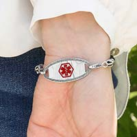 Woman wearing Black Macrame Medical ID Bracelet with stainless oval medical ID tag with border design and red caduceus