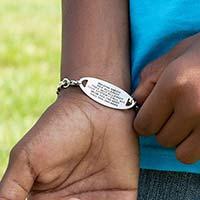 Boy showing custom laser engraved medical ID tag