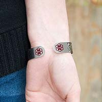 Woman wearing Filigree Medical Alert Cuff. Silver tone stainless cuff. Intricately scrolled design and red caduceus each end