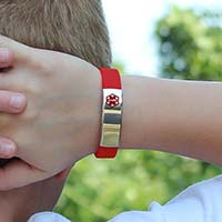 Child wearing red silicone activewear slim medical alert bracelet with stainless steel medical ID tag