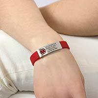 Woman wearing red silicone activewear slim medical alert bracelet with custom engraving