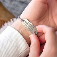 Woman showing custom laser engraved silver tone medical alert tag