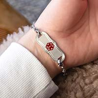 Woman showing silver medical ID tag with decorative edge and red medical caduceus symbol