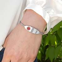 Woman wearing Micro Cuff Medical ID Bracelet. Slip-on silver-tone stainless bracelet with red caduceus