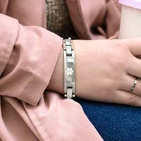 Woman wearing rose gold and silver two-tone linked medical ID bracelet