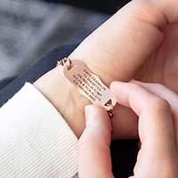 Woman showing custom laser engraved rose gold medical alert tag
