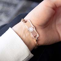 Woman showing rose gold medical alert tag with decorative edge and white medical caduceus