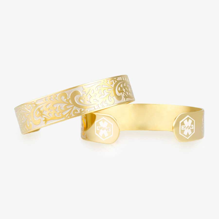 Gold tone medical alert with decorative filigree swirl pattern in pearl inlay with pearl medical alert symbols