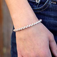 Woman wearing and showing the front of the Peyton Medical ID Bracelet with the cream and tan bolo leather band