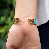 Woman wearing Key West Medical ID Cuff. Back of the cuff has a red caduceus on each end. Cuff has yellow gold background