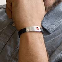 Man wearing black silicone Medical ID bracelet with silver tone stainless waterproof slip-on Med ID tag with red caduceus