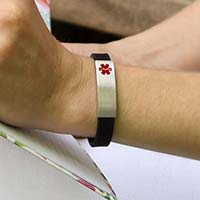 Woman outdoors opening mailbox wearing black silicone band bracelet with silver tone stainless Med ID tag with red caduceus