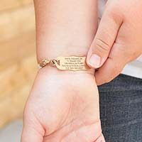 Girl wearing and showing engraving on the La Petite Med ID tag on the Nova Medical ID Bracelet, a white band with sparkles