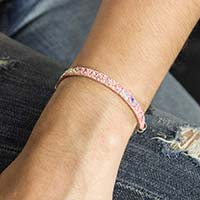 Girl wearing the Pixel Medical ID Bracelet, a 5 mm flat pink leather band with sparkles, with La Petite White Caduceus ID tag