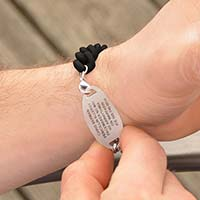 Woman holding a tennis racquet wearing Par For The Course Medical ID Bracelet, a black silicone band with engraving on ID tag