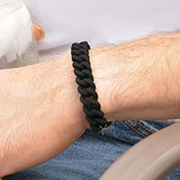Woman holding a tennis racquet wearing the Par For The Course Medical ID Bracelet, a black waterproof silicone band
