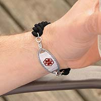 Woman holding a tennis racquet wearing Par For The Course Medical ID Bracelet, a black silicone band with Oval Border ID tag