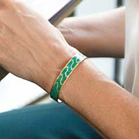 Woman wearing emerald and gold medical alert cuff with decorative geometric pattern