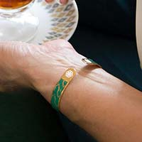 Woman showing medical caduceus symbols on the back of gold medical ID cuff