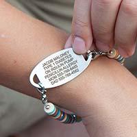 Boy flipping over medical alert tag to display medical details custom laser engraved on back of tag.