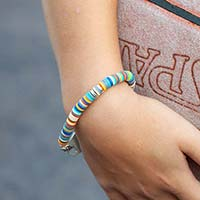 Young boy holding basketball and wearing colorful beaded stretch bracelet.