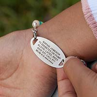 Little girl flipping over her medical ID tag to show medical details custom laser engraved on back of tag.