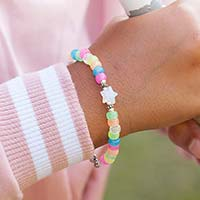 Young girl playing soft ball wearing colorful beaded medical ID bracelet with rainbow beads.