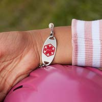 Little girl showing the medical alert tag on colorful medical ID bracelet with red caduceus facing forward.