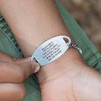 Little boy showing custom laser engraving on back of medical ID tag.